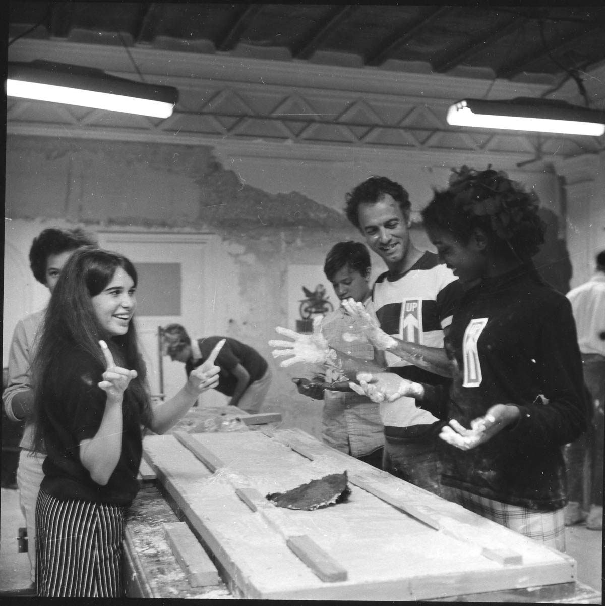 Students experiment with plaster, with sculptor Richard Randall (in striped shirt) leading the way, 1968