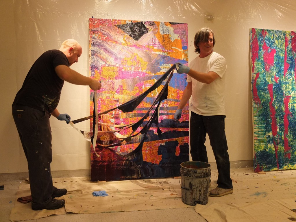 Jeremy and Ed tearing plastic wrap off their painting. Photo by Angela Lundberg.