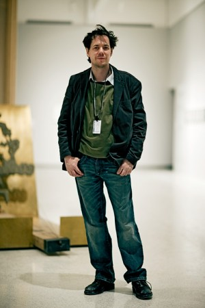 "Mark Manders, with part of ""Life-Size Scene with Revealed"" visible in background"