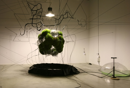 Tomás Saraceno, 32SW Stay Green/Flying Garden/Air-Port-City, 2007. Pillows with pressurized air, webbing, covered with black felt, grass, solar flexible panels, electrical cables, battery, solar pump, water supply system. 192-15/16 in. diameter. Courtesy the artist and Tanya Bonakdar Gallery, New York