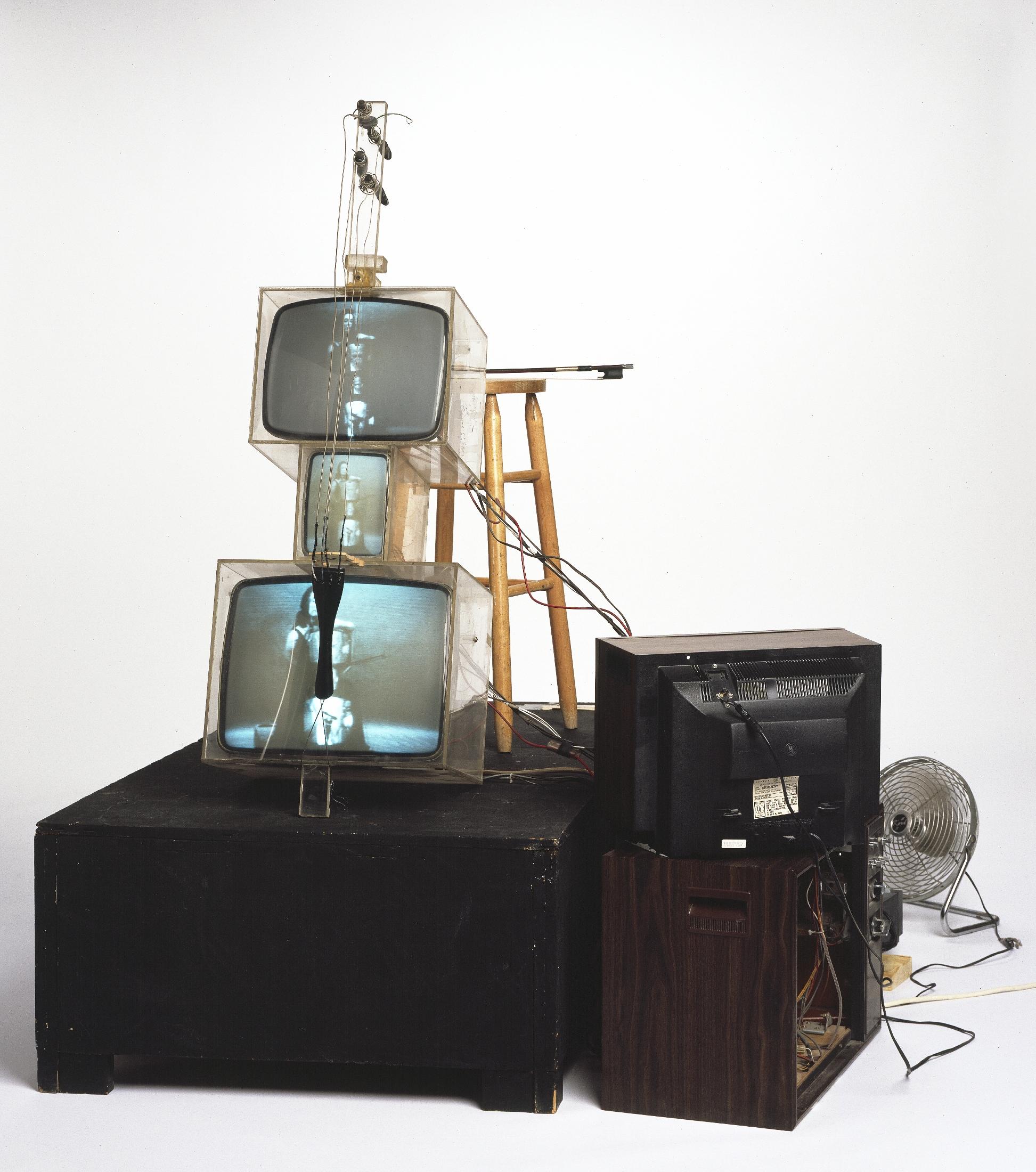 Nam June Paik, 'TV Cello' (1971), video tubes, TV chassis, plexiglass boxes, electronics, wiring, wood base, fan, stool, photograph. © Estate of Nam June Paik. Courtesy Walker Art Cente
