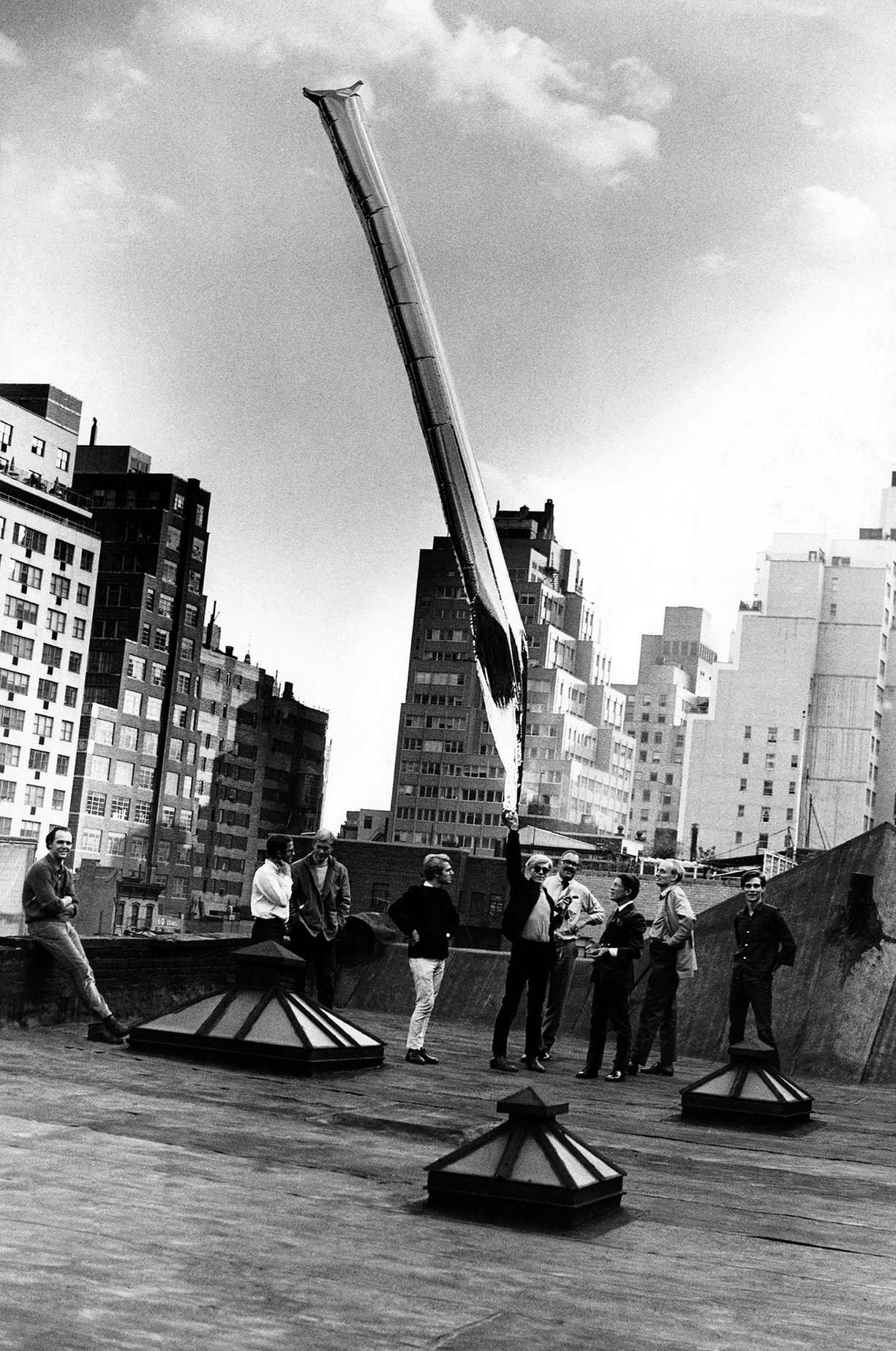 Andy Warhol, Gerard Malanga and others release a silver mylar balloon from the Factory rooftop on 47th Street. Photo by Billy Name