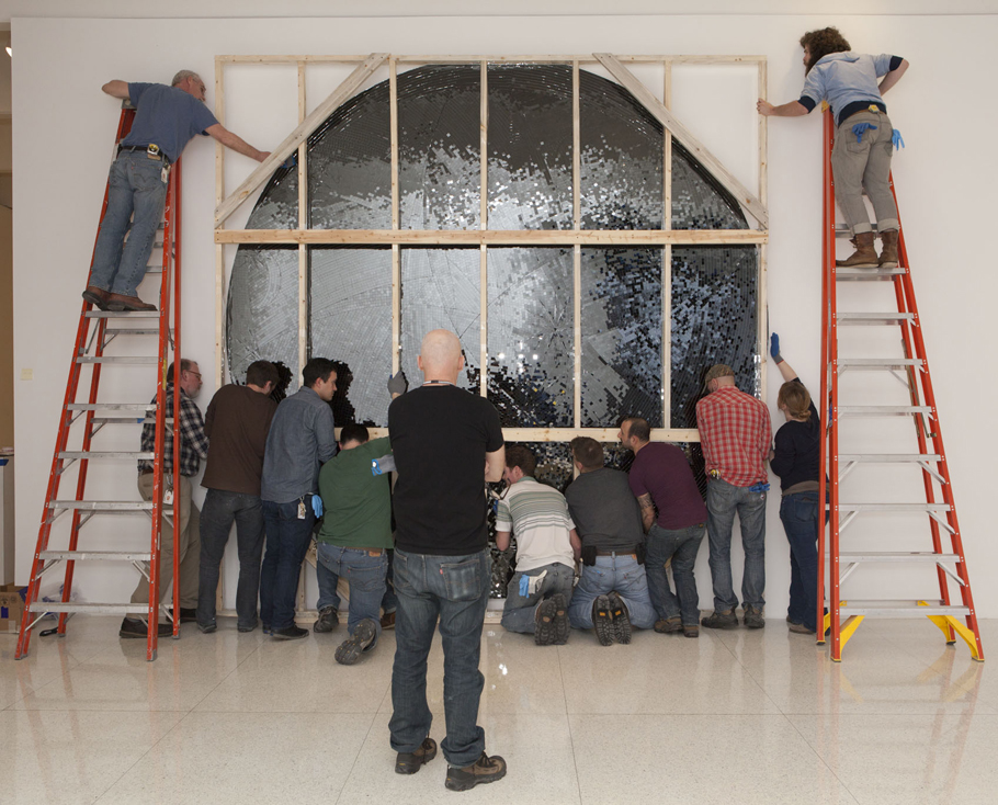 It takes many hands—and two ladders—to install this mirror mosaic piece, Untitled, 2011.