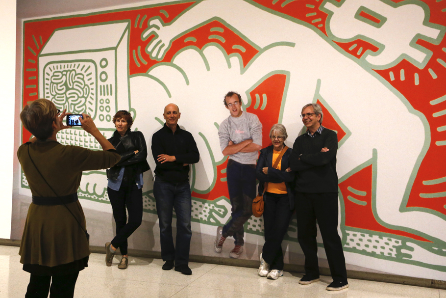 Visitors posing with a photo mural of Keith Haring.