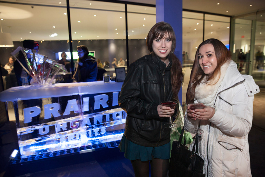 Women holding drinks in front of ice bar.